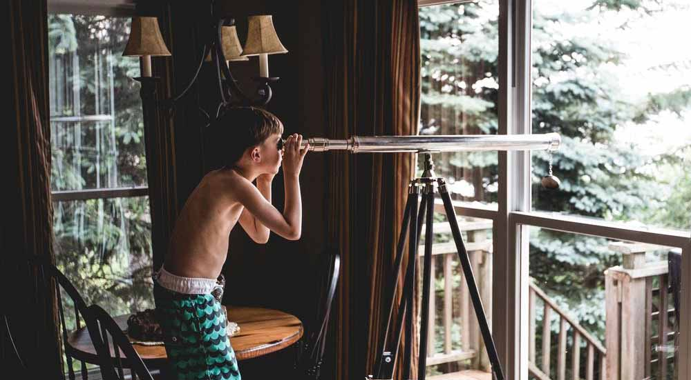 Photo of a curious kid looking through a telescope